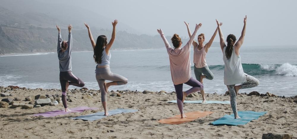 group of women doing yoga on a beach
